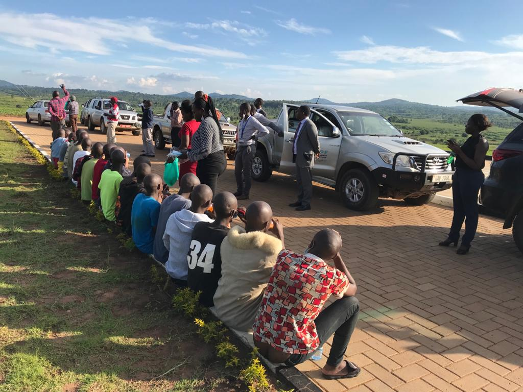 The 19 imprisoned LGBT community members in Uganda await transportation back home from Kitalya Prison after being released today, 50 days after their arrest. (HRAPF photo)