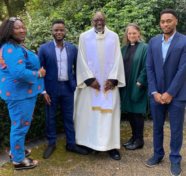 Celebrating the ordination of the Rev. Jide Macaulay are (left to right) LadyPhyll, Dan Yomi, the Rev. Macaulay, the Rev. Cathy Bird, and Macaulay's partner Moses.
