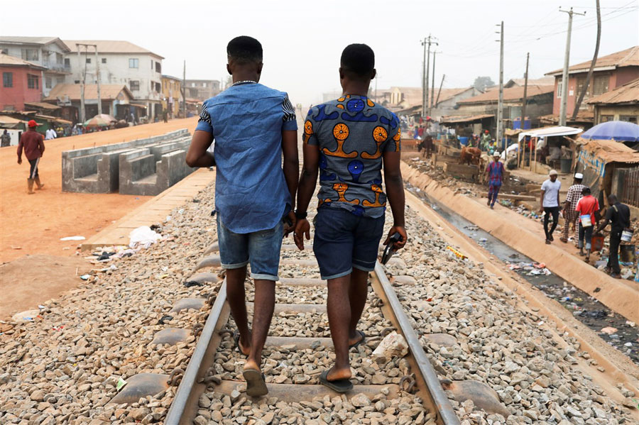 Chris Agiriga, 23, one of the men arrested on charges of public display of affection with members of the same sex, walks with a friend on the streets of Lagos, Nigeria, last February. (Temilade Adelaja photo courtesy of Reuters)