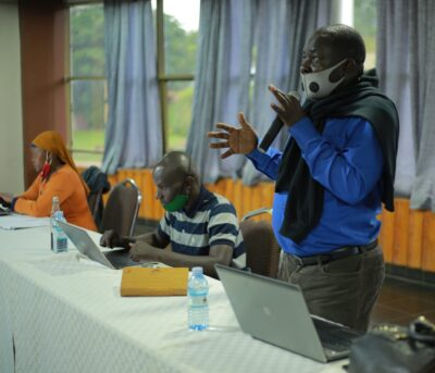 LGBT activist/journalist Kikonyogo Kivumbi shares with participants. To the left is Umaru Wesaala, a Ugandan social justice blogger.